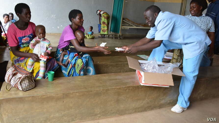 Medical workers distribute nutritious foods to mothers in Zomba district for their children who are at the verge of suffering malnutrition due to the food shortage. (L. Masina/VOA)