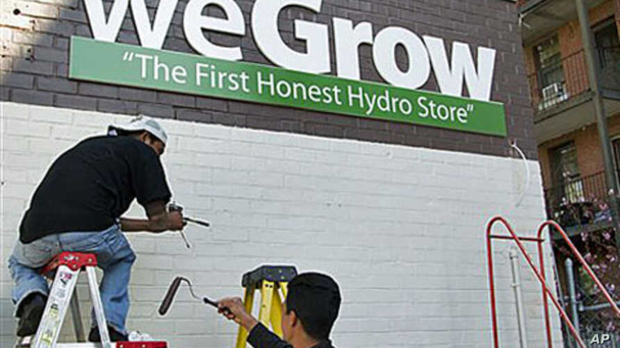 Workers put the finishing touches on the side of a building that will house a weGrow store in preparation for its opening on April 6, in northeast Washington, DC, March 29, 2012.
