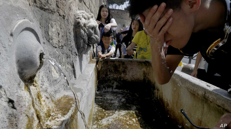 Tourists refresh themselves at a fountain in Rome, Aug. 9, 2017.