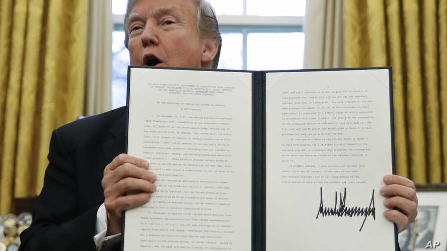 "President Donald Trump holds up one of the Section 201 actions that he signed during a ceremony in the Oval Office of the White House in Washington, Jan. 23, 2018. Trump says he is imposing new tariffs to ""protect American jobs and American workers."""