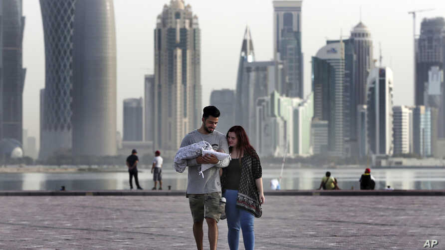 A couple take a weekend walk with their new born baby along the waterfront, in Doha, Qatar, May 4, 2018.