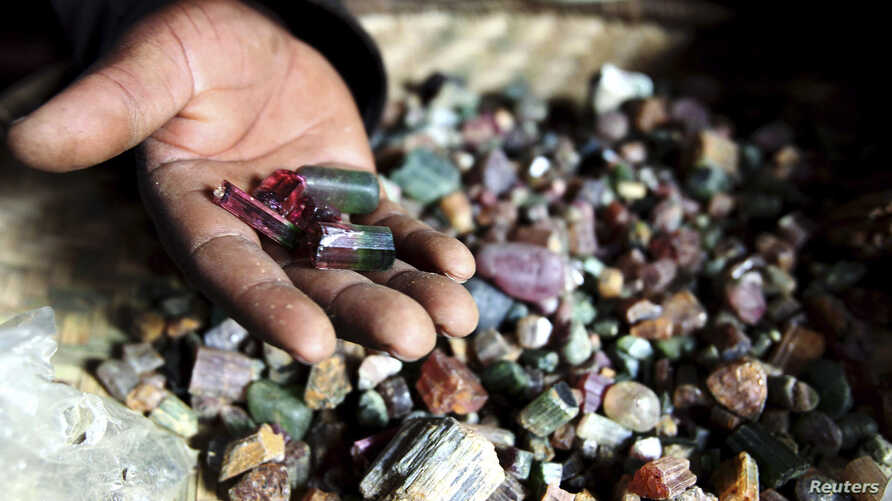 FILE - A Congolese mineral trader displays semi-precious tourmaline gem stones in a mud hut at Numbi in eastern Congo.