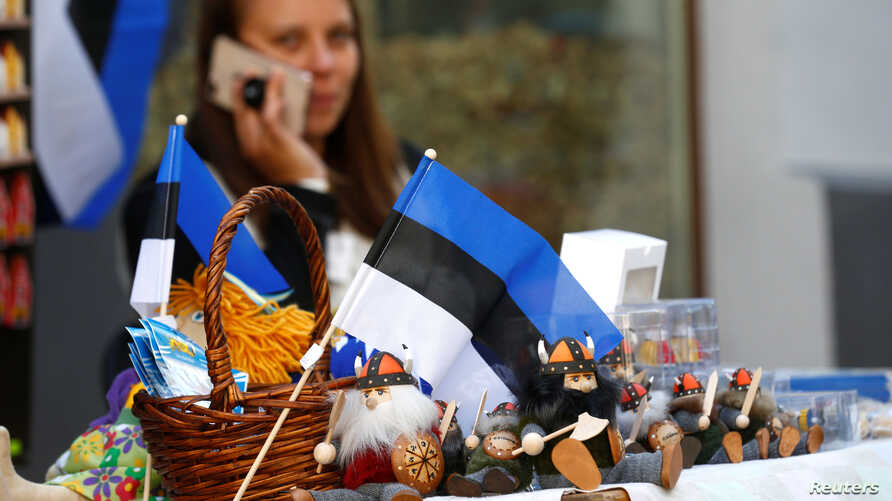 FILE - An Estonian national flag is seen as a street vendor speaks on her phone in Tallinn, Estonia, May 31, 2018.