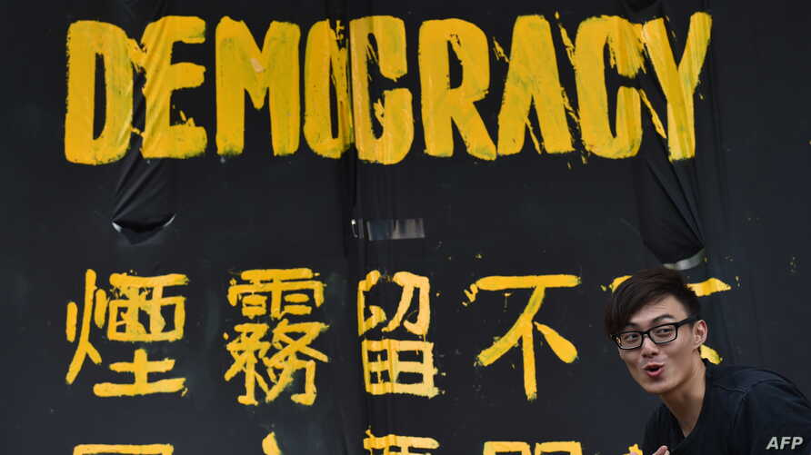 A pro-democracy protester stands next to a banner in Hong Kong, Sept. 30, 2014.