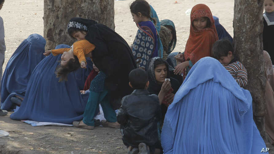 Afghan refugee families sit outside the government registration office preparing to leave for their homeland, in Peshawar, Pakistan, March 14, 2017.