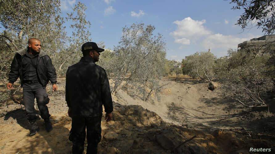 Palestinian policemen loyal to Hamas inspect the scene of an Israeli air strike in the northern Gaza Strip Oct. 28, 2013.