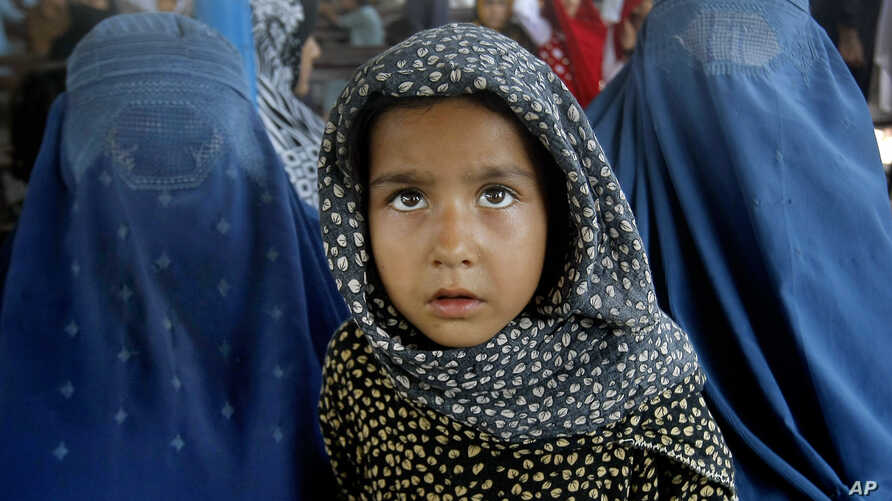 Afghan refugees wait for their documents to go back to Afghanistan at the UNHCR's Repatriation Center in Peshawar, Pakistan on June 23, 2016.