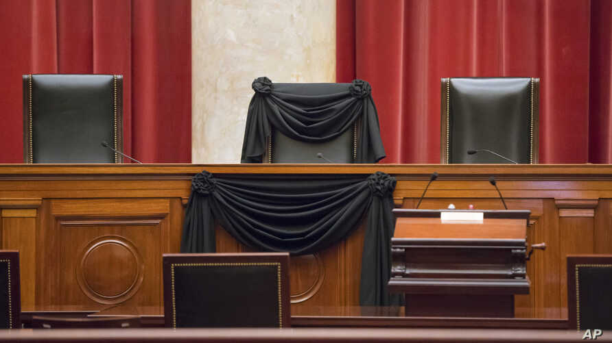 Supreme Court Justice Antonin Scalia's courtroom chair is draped in black to mark his death as part of a tradition that dates to the 19th century, Tuesday, Feb. 16, 2016, at the Supreme Court in Washington.