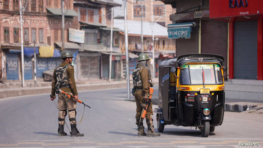 Indian police officer stop an auto-rickshaw after Kashmiri separatists called for a day-long strike against the recent killings in Kashmir, in downtown Srinagar, Apr. 2, 2018.