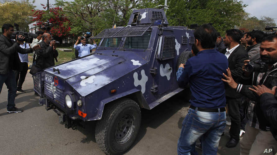 """Pakistani journalists surround an armored vehicle carrying Rao Anwar, a police officer accused of killing a 27-year-old man in an allegedly """"stage-managed"""" shootout in the port city of Karachi that sparked outrage on the part of Pakistan's tribal com"""