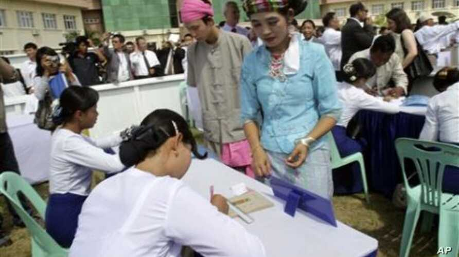 Volunteers in Shan ethnic traditional costume enroll to get ballots in a demonstration on voting for the upcoming general election, in Naypyitaw, Burma's new administrative capital, 18 Oct 2010