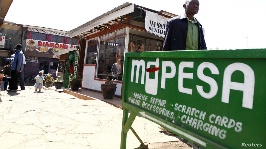 FILE - A man walks away from a retail mobile money transfer shop in Ngong township in the outskirts of Kenya's capital Nairobi.