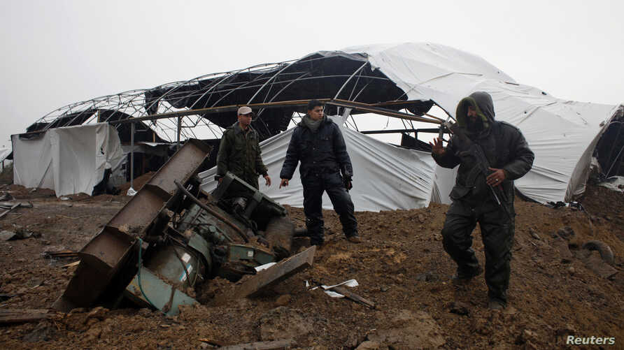 Members of the Palestinian security forces loyal to Hamas inspect the damage after Israeli air strikes on smuggling tunnels in Rafah in the southern Gaza Strip, March 13, 2014.