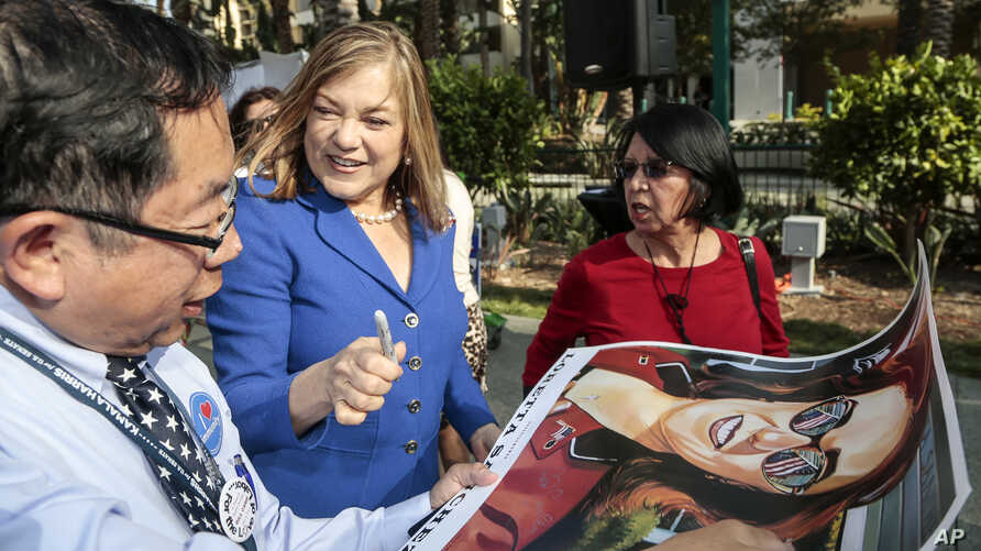 FILE - U.S. Rep. Loretta Sanchez, second from left, autographs a campaign poster for a supporter in Anaheim, Calif., May 16, 2015.