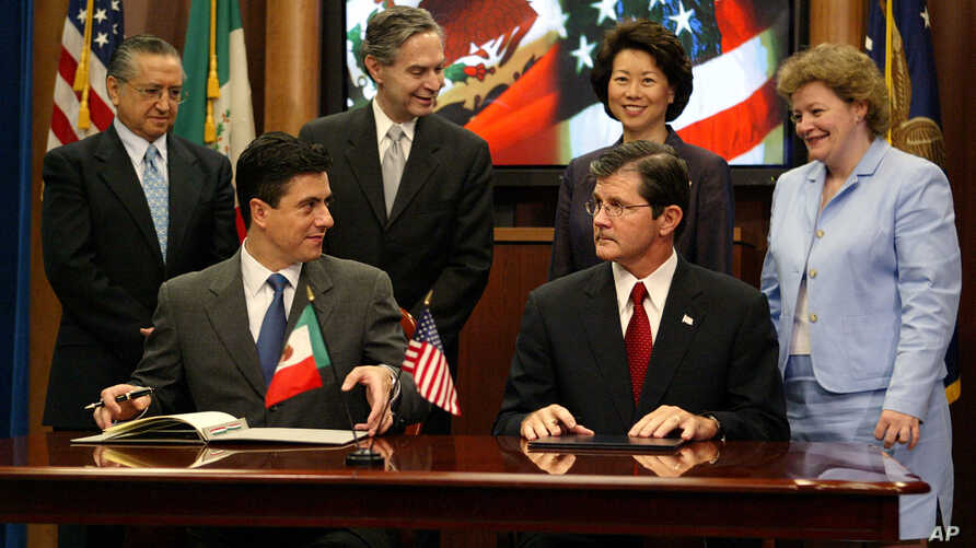FILE - Mexican Foreign Affairs Undersecretary for North America Geronimo Gutierrez (front left) and Assistant Secretary of Labor for Occupational Safety and Health John Henshaw (front right) pause as they sign a workplace safety agreement, July 21, 2