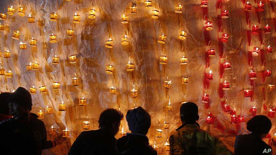 In this photo taken on Wednesday, Nov 25, 2015, contestants arrange paper lanterns on the fire balloon during annual hot air balloon festival in Pyin Oo Lwin, Mandalay Division, Myanmar.