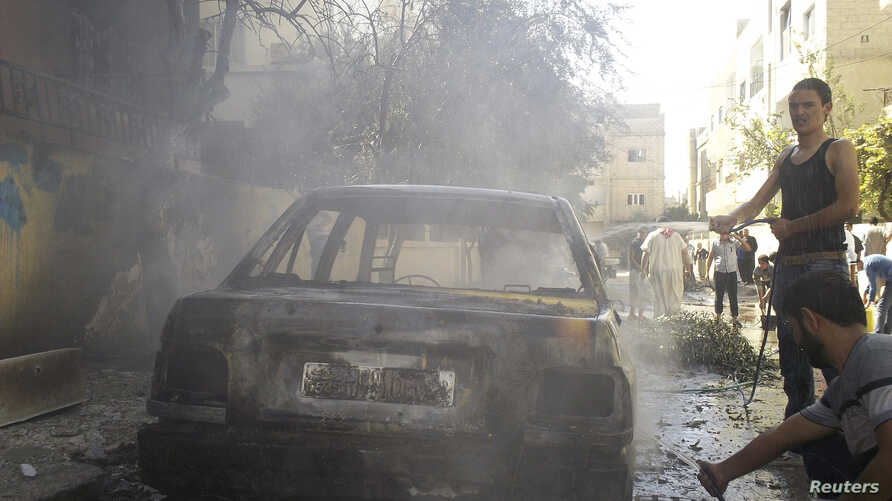 Residents stand next to a damaged car after shelling by forces loyal to Syria's President Bashar al-Assad at al-Saad near Deraa November 3, 2012.
