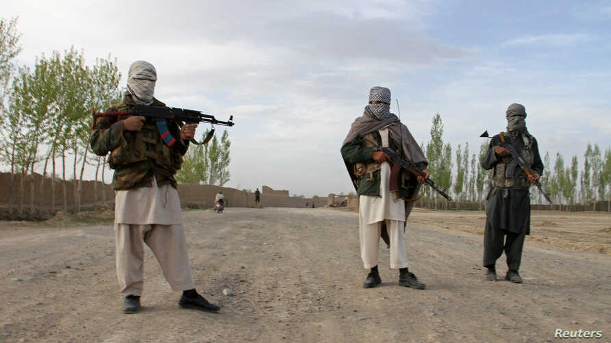 Members of the Taliban stand at the site of the execution of three men in Ghazni province