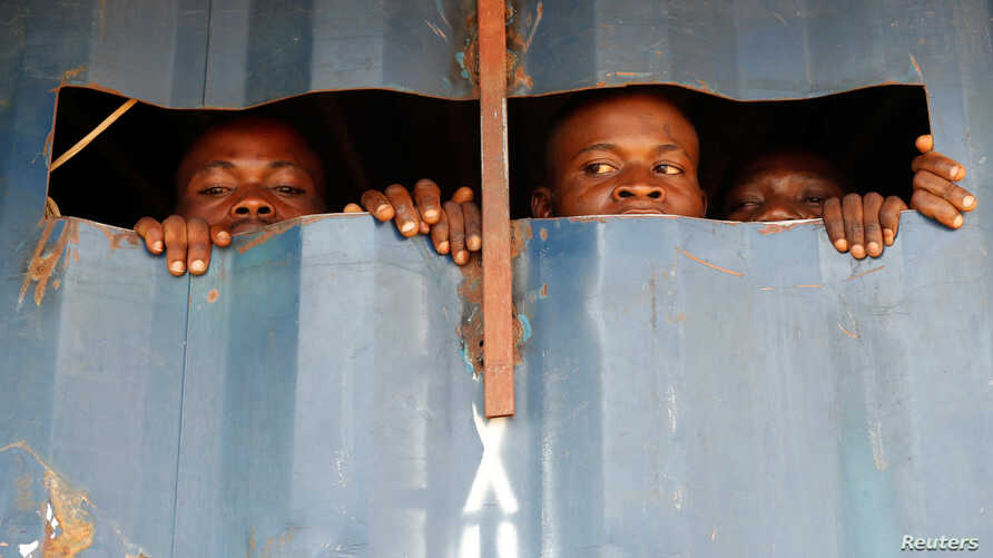 Detained Mai-Mai Yakutumba rebels, captured by Congolese soldiers from the Armed Forces of the Democratic Republic of Congo (FARDC) look out of a container in Namoya, Maniema Province, eastern Democratic Republic of Congo.