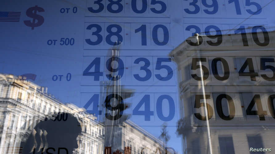 FILE - A woman is reflected in a window with a board displaying currency exchange rates in St. Petersburg, Russia, Sept. 16, 2014.