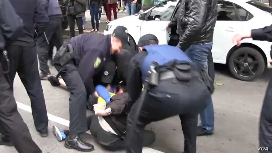 Assailants attacked gay and transgender rights activists and torched a rainbow flag at a small rally in the Ukrainian city of Kharkiv.