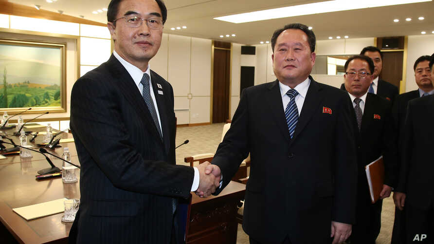 South Korean Unification Minister Cho Myoung-gyon, left, shakes hands with the head of North Korean delegation Ri Son Gwon after their meeting at the Panmunjom in the Demilitarized Zone in Paju, South Korea, Jan. 9, 2018.