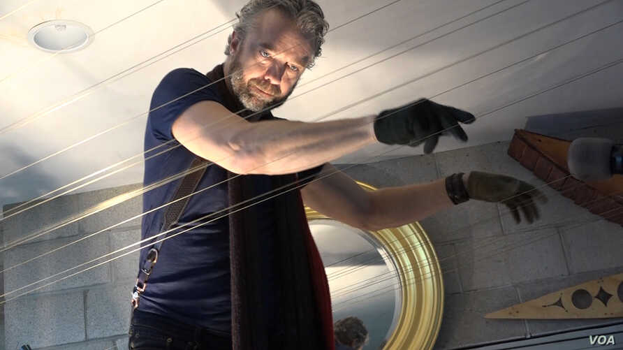 Musician and inventor William Close achieved the world record for longest stringed instrument for the 2014 performance on his Earth Harp in Singapore. (MSullivan/VOA)
