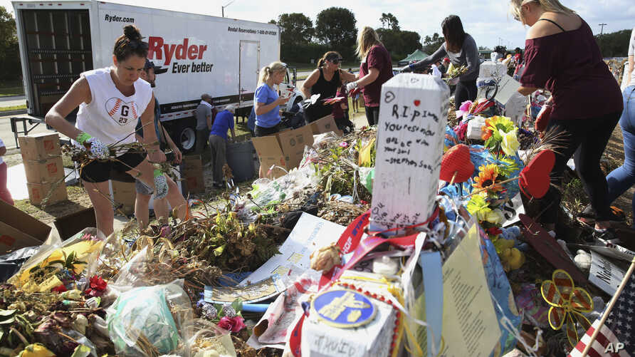 Volunteers, students and parents sort items left at the memorial site for the 17 students and faculty killed at Marjory Stoneman Douglas High School, Wednesday, March 28, 2018 in Parkland, Florida.