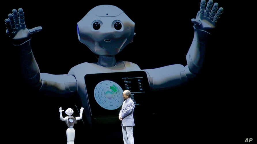 FILE - SoftBank Corp. CEO Masayoshi Son speaks with the company's companion robot Pepper during a press conference in Maihama, near Tokyo,  June 18, 2015.