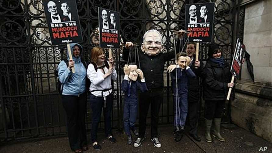 Protester wears a Rupert Murdoch mask, holds puppets of British PM David Cameron, left, and Culture Secretary Jeremy Hunt, at a press ethics inquiry being held at High Court in London, April 25, 2012.