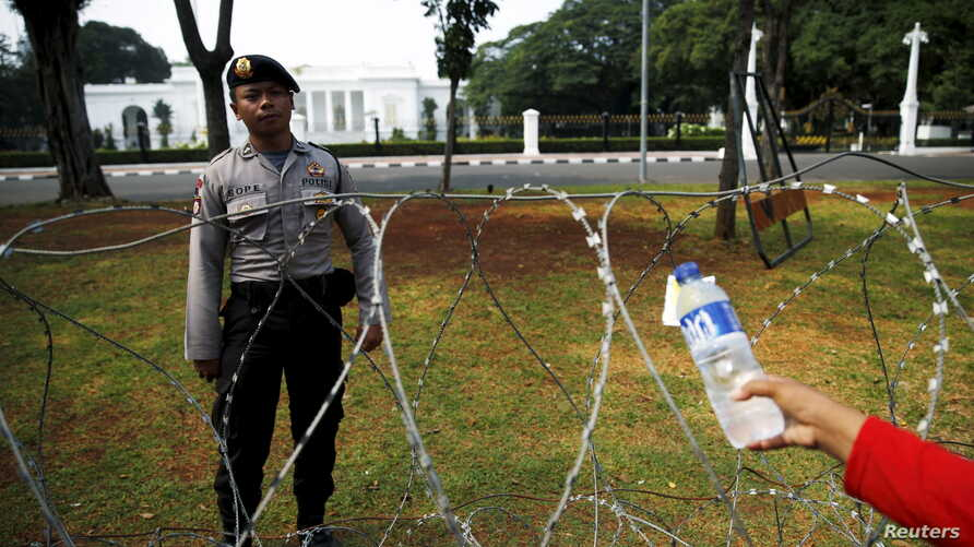 An Indonesian street vendor offers a drink to a policeman as he guards in front of the Presidential Palace during a workers protest in Jakarta, Oct. 15, 2015.