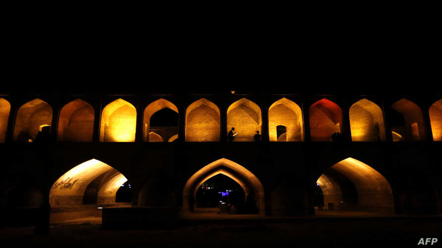"""Iranians walk next to the """"Si-o-Se Pol"""" bridge (33 Arches bridge), April 12, 2018, over the Zayandeh Rud river in Isfahan, which now runs dry because of water extraction before it reaches the city. The 295-meter-long bridge was completed in 1596 by I"""