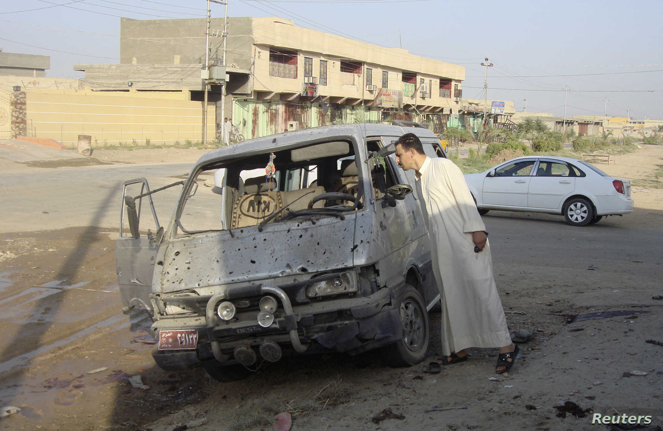 A resident inspects a damaged vehicle a day after a car bomb attack in Dujail, 50 kilometers north of Baghdad, Aug. 23, 2013.