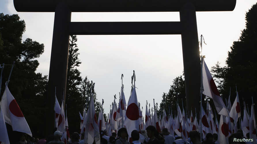 """Members of nationalist movement """"Ganbare Nippon"""" raise Japanese national flags towards the huge Torii gate at the Yasukuni shrine while paying tribute to the war dead in Tokyo August 15, 2013, on the 68th anniversary of Japan's surrender in World War"""