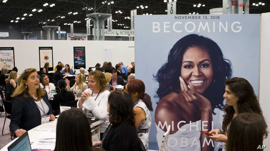 """FILE - A poster for former first lady Michelle Obama's memoir, """"Becoming,"""" is displayed at the Penguin Random House exhibit, May 31, 2018, at Book Expo in New York. The book went on sale this month."""