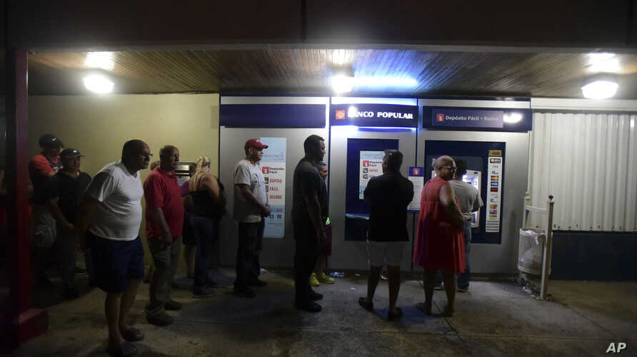 Clients of Popular Bank of Puerto Rico wait in line at the Carolina Shopping Court branch to withdraw cash from their accounts after the passage of Hurricane Maria, in Carolina, Puerto Rico, September 27, 2017.