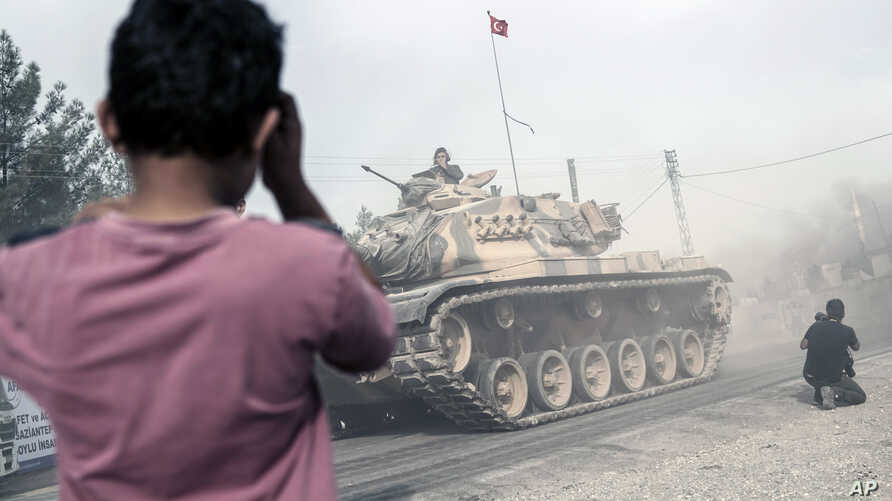 A boy looks at Turkish army tanks and armored personnel carriers moving toward the Syrian border, in Karkamis, Turkey, Aug. 25, 2016.