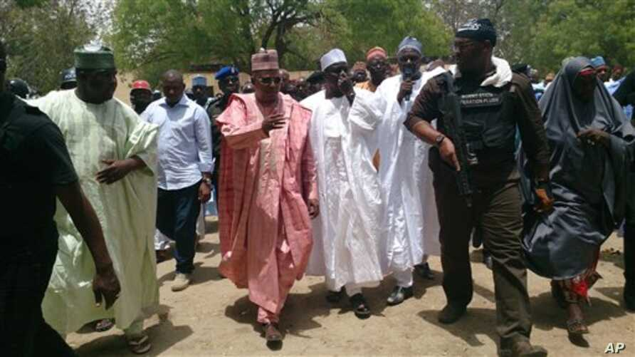 In this photo taken  Monday, April, 21. 2014. Borno state governor Kashim Shettima, centre, visit  government secondary school Chibok, were gunmen abducted more than 200 students in Chibok, Nigeria. Nigerian parents say more than 200 girls and young