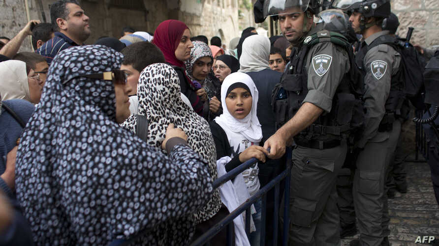 Palestinian Muslim worshippers wait as Israeli border guards have their documents and belongings checked at the entrance of al-Aqsa mosque compound in Jerusalem's Old city, April 20, 2014.