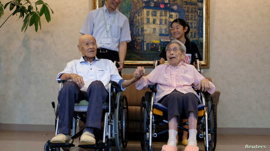 The world's oldest living married couple, Masao Matsumoto and Miyako Matsumoto, pose for a photo with their great-grandchild and and a caregiver at a nursing home, in Takamatsu, Kagawa prefecture, Japan, Sept. 4, 2018.