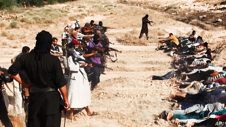 FILE - Image posted on a militant website on June 14, 2014, appears to show militants from the Islamic State group taking aim at captured Iraqi soldiers wearing plain clothes after taking over a base in Tikrit, Iraq.