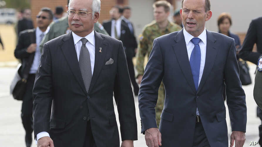 Malaysian Prime Minister Najib Razak, left, walks along the tarmac with Australian Prime Minister Tony Abbott on their way to meet crew members involved in search of wreckage and debris of the missing Malaysia Airlines MH370 in Perth, Australia, Thur