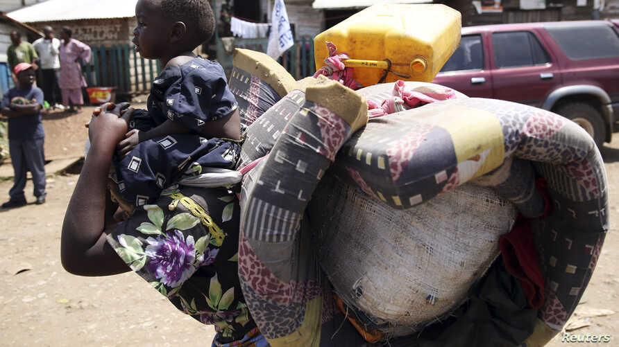 A woman carries her child in Minova, 45 kilometers west of Goma, DRC, November 26, 2012.