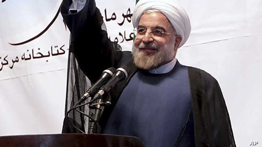 Iran's President Hassan Rouhani waves to participants while he attends a ceremony to mark the beginning of the universities academic year, at the Tehran University, in Tehran, Iran, Oct. 14, 2013.