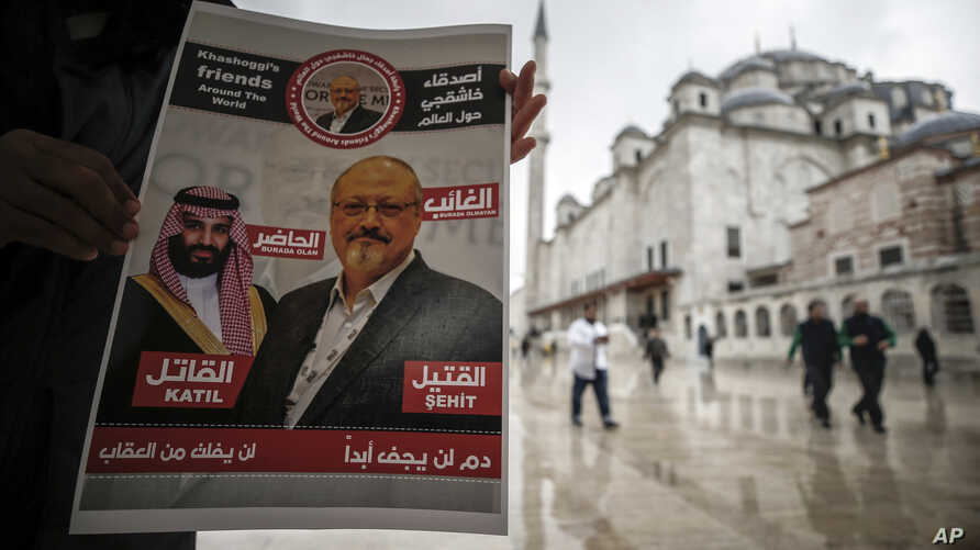 """A man holds a poster showing images of Saudi Crown Prince Muhammed bin Salman and of journalist writer Jamal Khashoggi, describing the prince as """"assassin"""" and Khashoggi as """"martyr"""" during funeral prayers in absentia for Khashoggi who was killed last"""