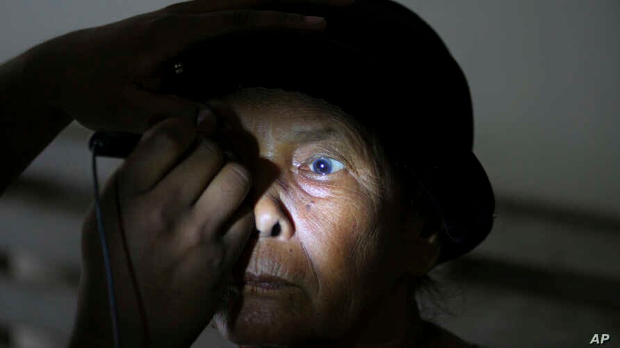 FILE -  a patient takes an eye examine at a military hospital in Padang Sidempuan, North Sumatra, Indonesia, Nov. 3, 2012..