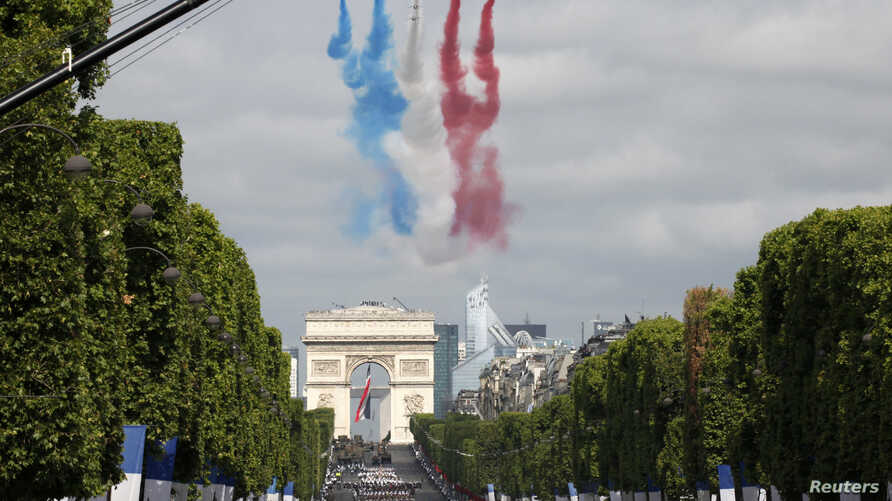 Alphajets from the French Air Force Patrouille de France in the formation of a Croix de Lorraine cross and releasing trails of red, white and blue smoke, colors of French national flag, fly over the Champs-Elysees avenue during the traditional Bastil