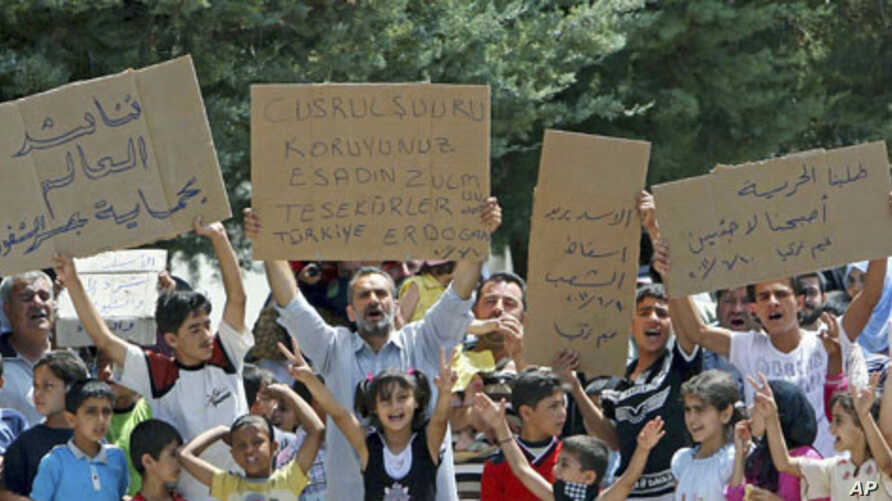 Syrian refugees hold banners - second from left reads 'Protect Jisr al-Shughour from Bashar al-Assad. Thanks to Turkey-Erdogan' - and chant slogans at Altinozu refugee camp in the Turkish border town of Altinozu in Hatay province, June 10, 2011