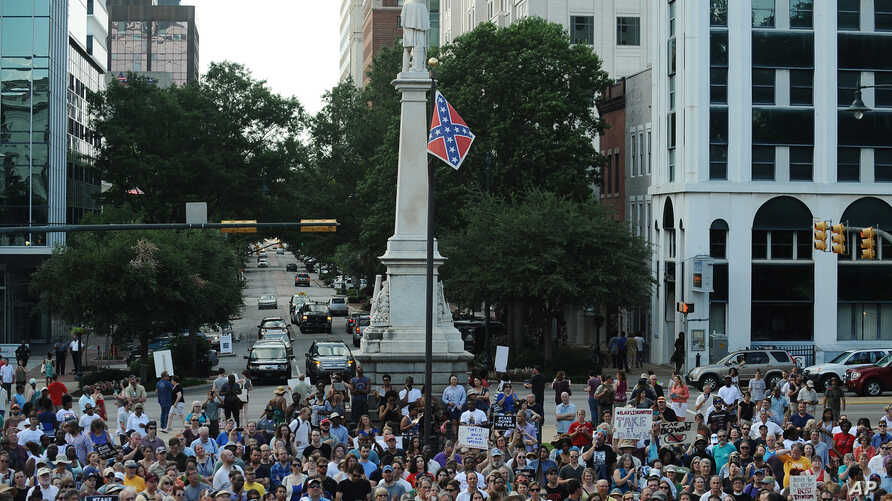 Protesters stand near a flying Confederate flag during a rally in support of its removal from the South Carolina Statehouse grounds in Columbia, June 20, 2015.