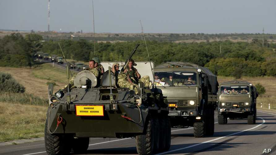 Russian military vehicles maneuver on a road 15 kilometers (9 miles) from the Ukrainian border in the Rostov-on-Don region, Russia, Aug. 15, 2014.
